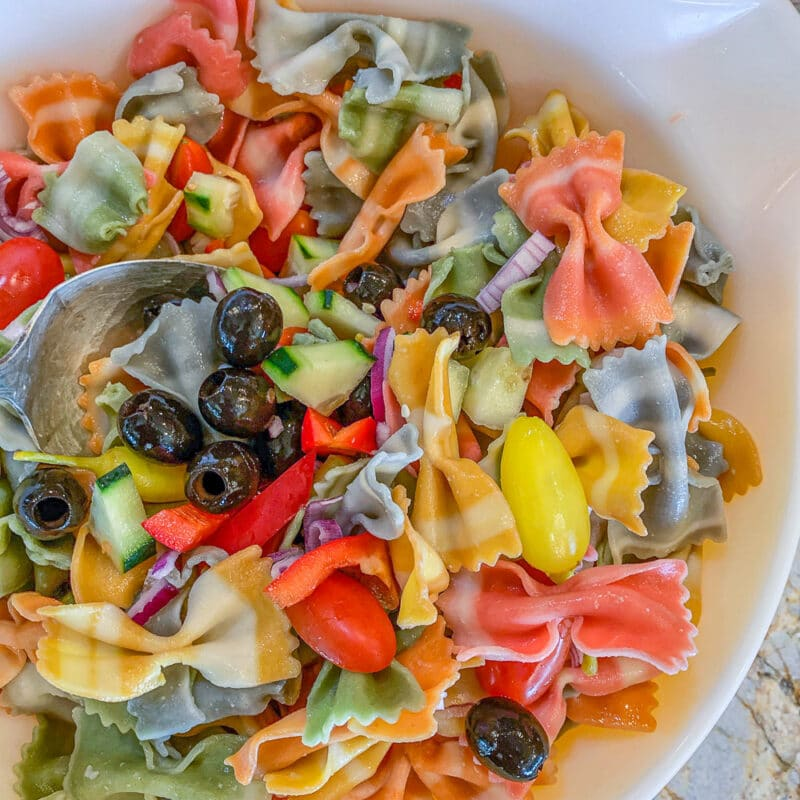 pasta salad being mixed in a bowl