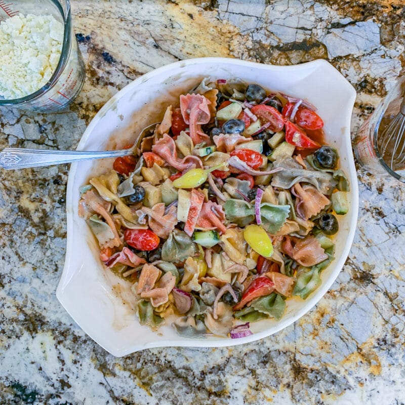 mixing pasta salad in a white bowl