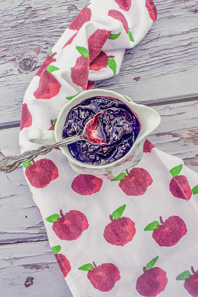 red fruit sauce in a serving dish over a cloth napkin