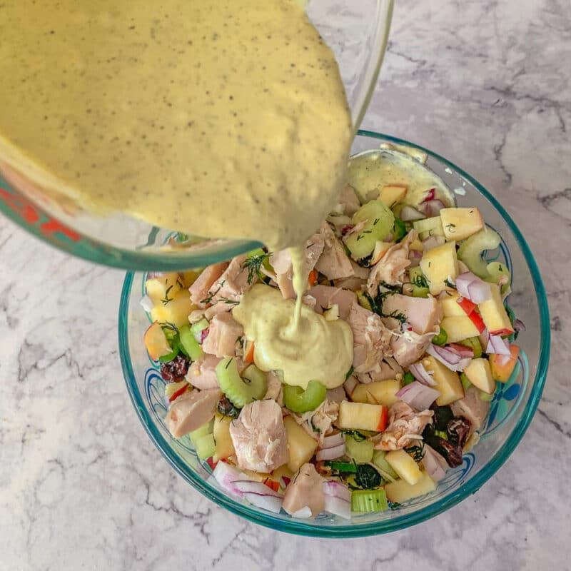 pouring salad dressing over chicken salad ingredients in a glass bowl