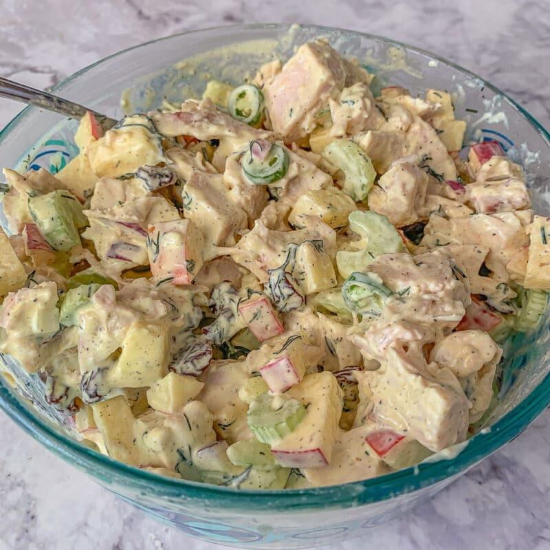 chicken salad in a glass bowl on a marbled counter