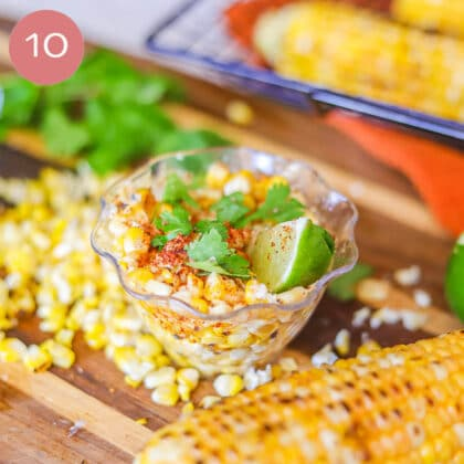 corn on the cob in a plastic cup with corn on the cob, cilantro, and cheese scattered around it