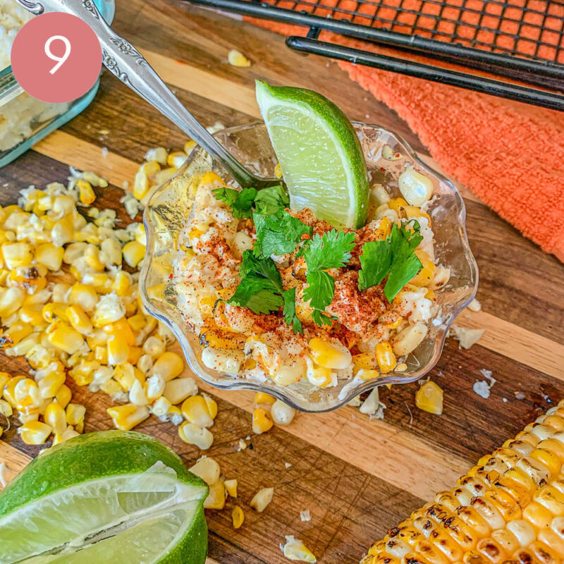 corn kernels in a plastic cup with a slice of lime and cilantro over a cutting board