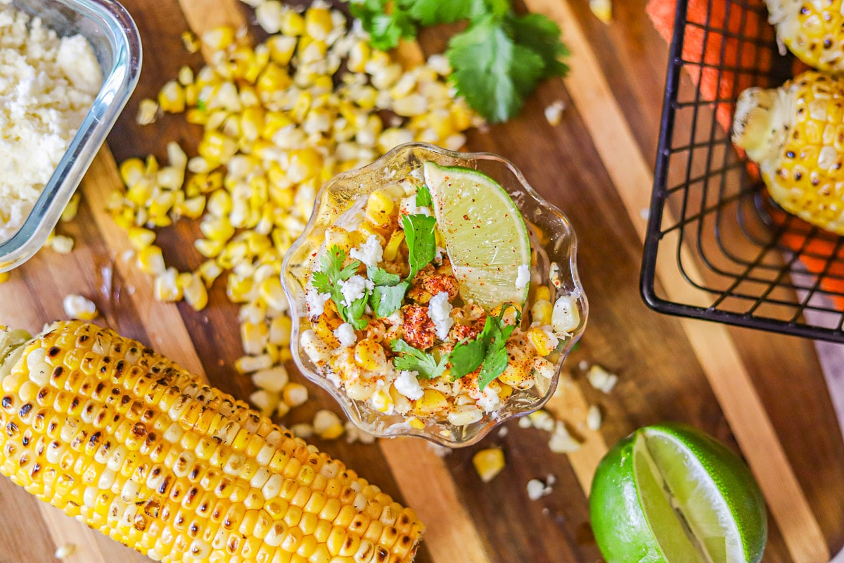 elote/corn in a cup with limes, cheese, and cilantro