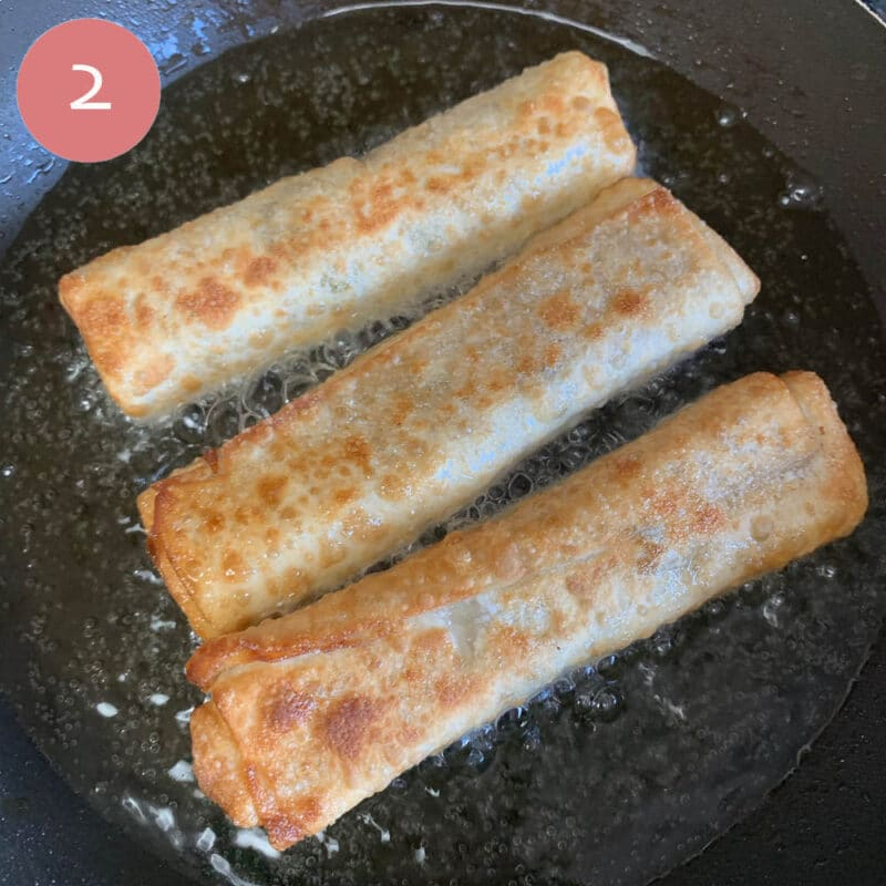 3 golden fried egg rolls in hot oil being fried