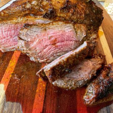 sliced medium rare oven trip roast on a cutting board