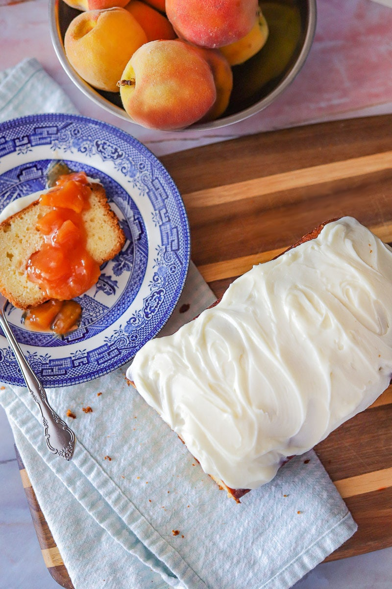 peach cobbler pound cake with peaches on the side along with a sliced piece on a blue plate over a checkered blue napkin