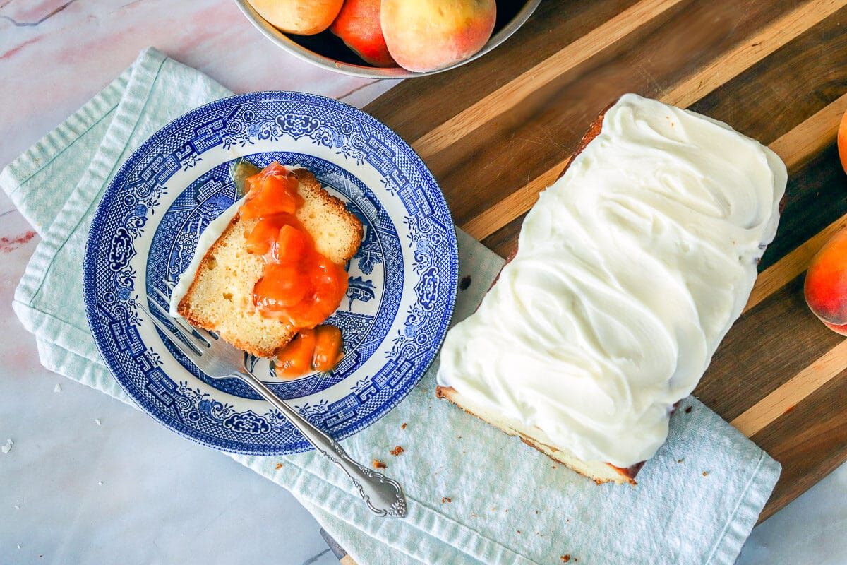 frosted Peach Cobbler Pound Cake with a slice on a blue plate with peaches around them