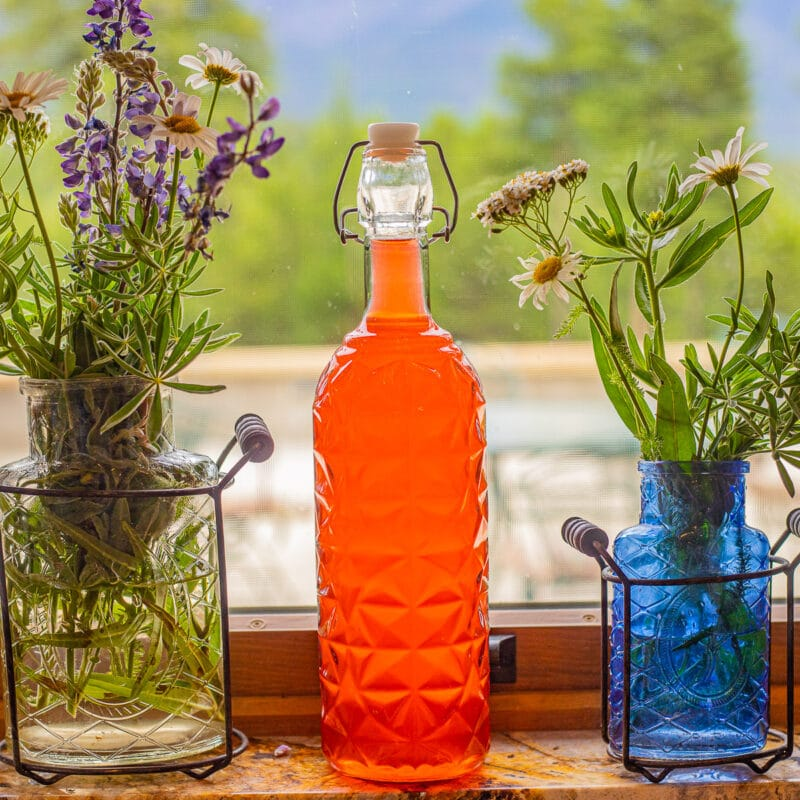 rhubarb gin in a bottle on a window with wild flowers on each side