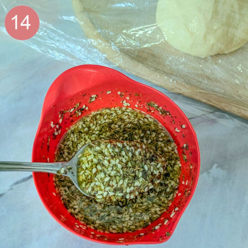 stirring zaatar and oil in a small red bowl