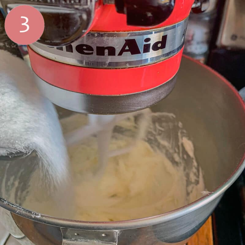 a red standmixer running with sugar being added to it