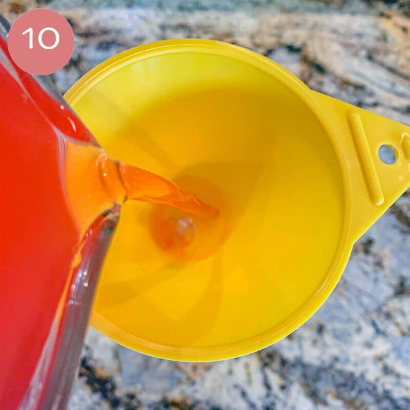 pouring rhubarb gin into a yellow funnel