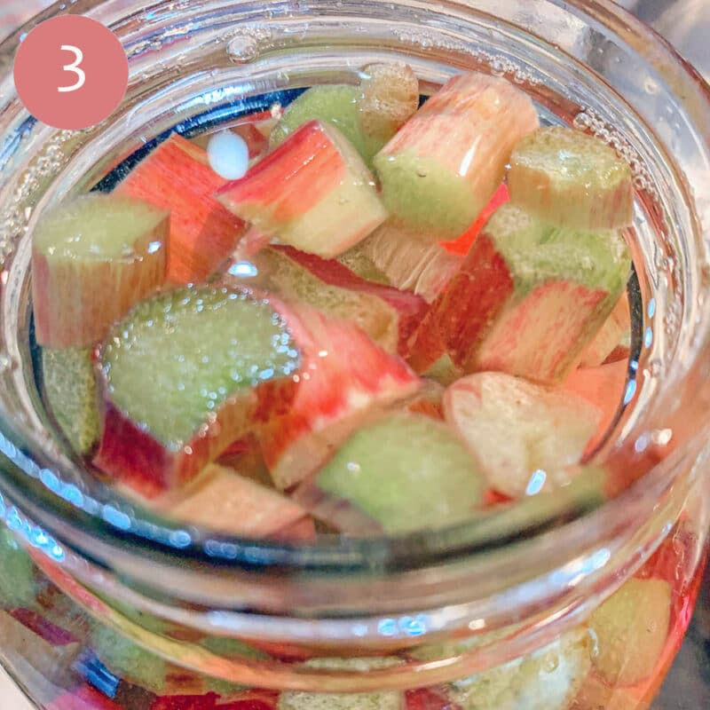 chopped rhubarb in a mason jar with alcohol over it