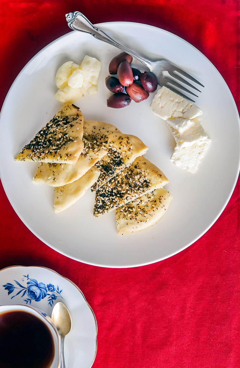 a white plate with cheese, black olives and Manaeesh bread cut in triangles with a red background and a glass of tea
