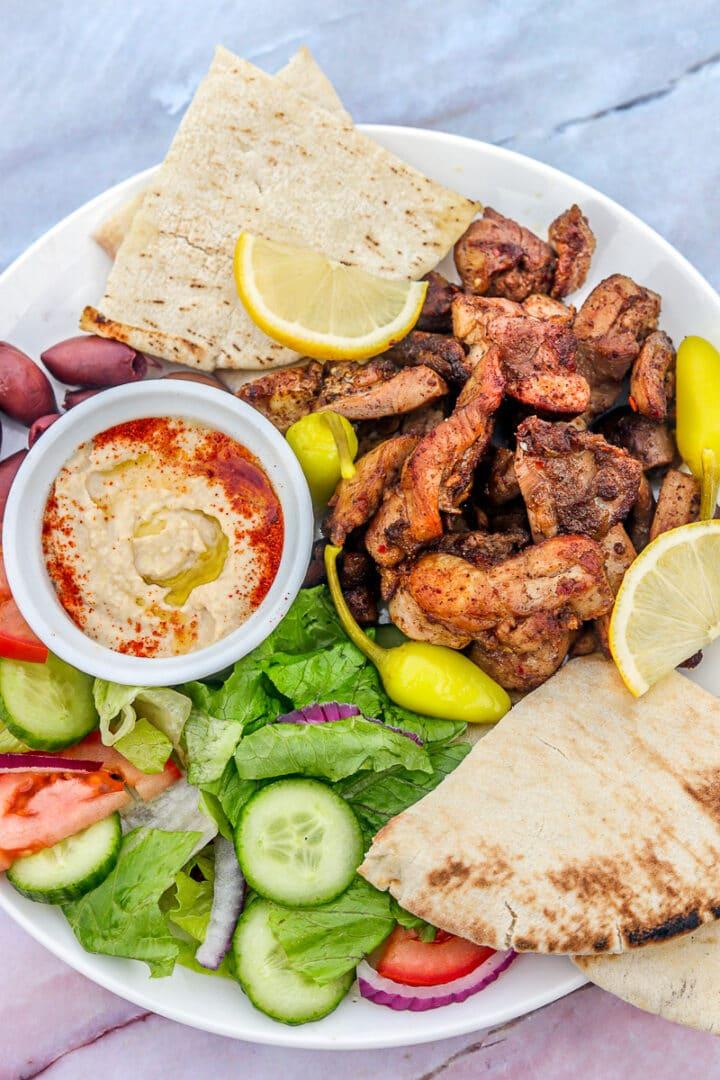 shawarma plate with chicken, salad, hummus, and pita bread