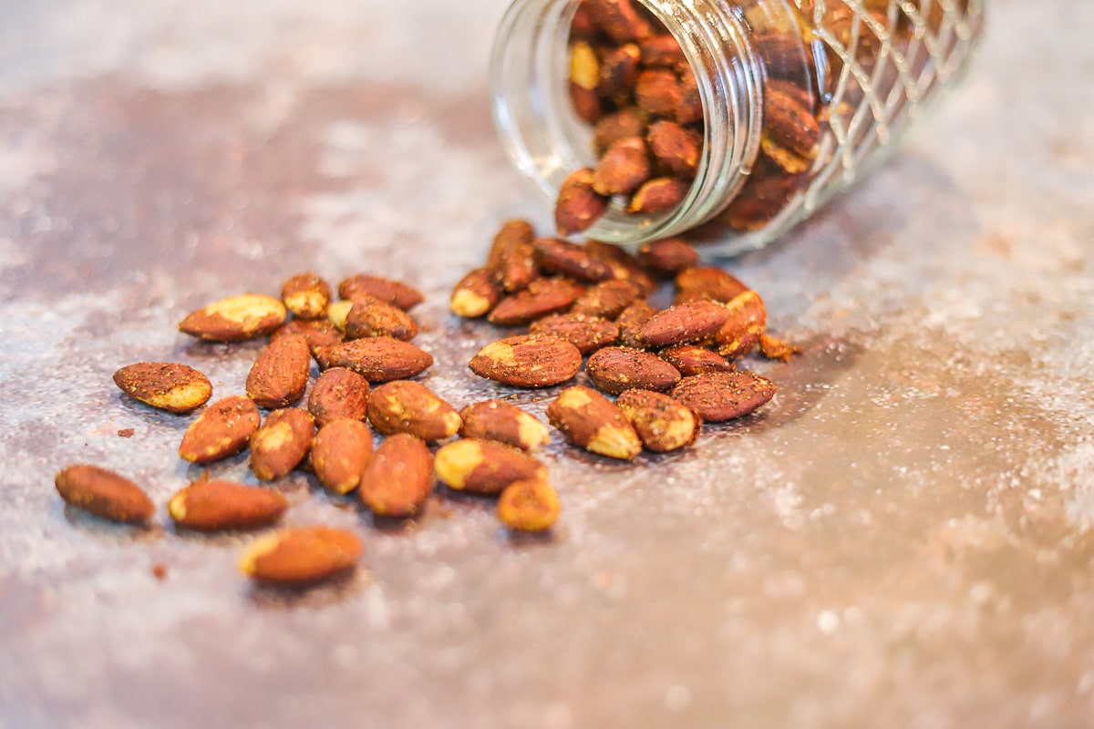 almonds spilling from a jar onto the counter