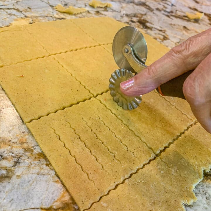 using a pastry cutter to make cuts in cookie dough