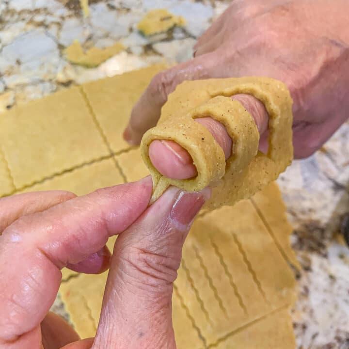 pinching Chebakia dough over a finger