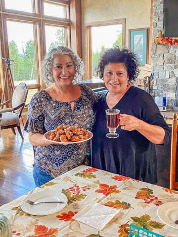 two ladies, one holding a plate of cookies, the other a glass of tea