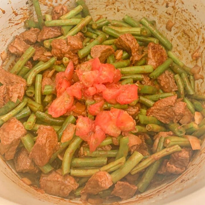 stew meat and green beans covered with diced tomatoes in an instant pot