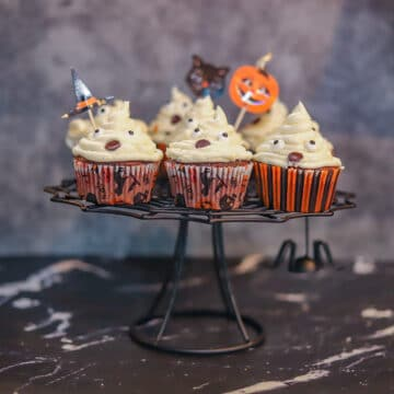 ghost cupcakes on a black cake stand
