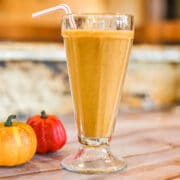 pumpkin protein shake in a tall glass with 2 small pumpkins next to it