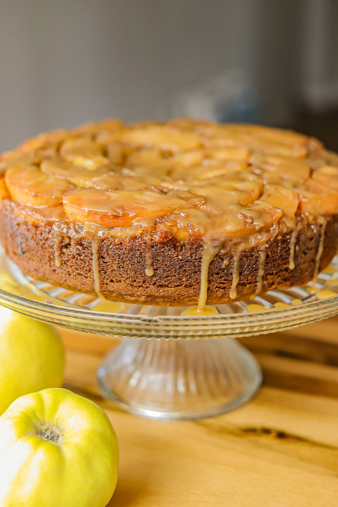 quince cake on a cake stand with some more quince on the side