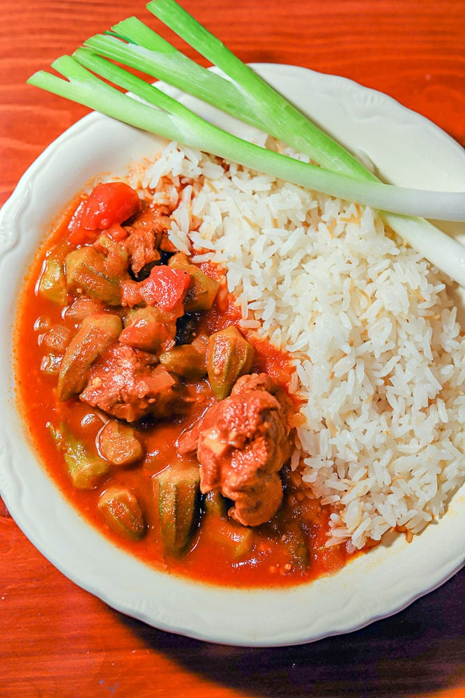 """Okra Ladies Fingers stew or """"bamia"""" with rice in a white plate with red background"""