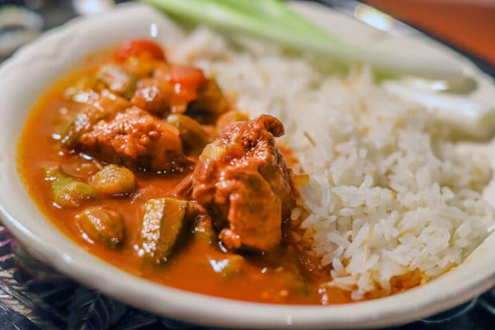 ladies fingers okra stew or bamia and white rice in a white bowl