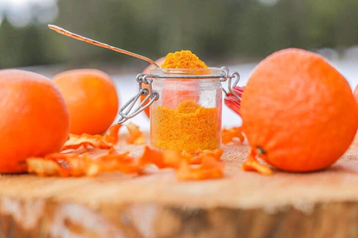 orange peel powder in a spoon on a wooden slab with oranges around it