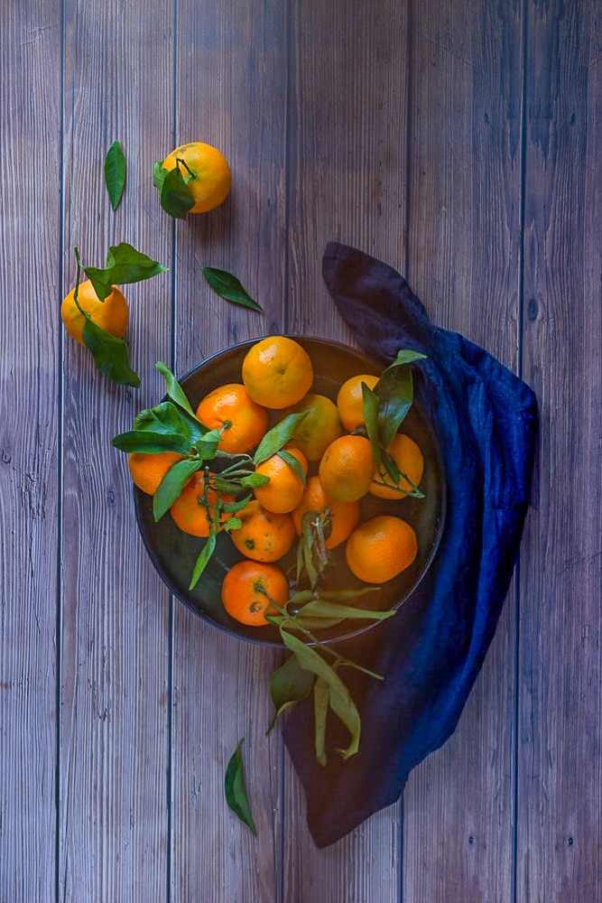 oranges in a plate with a blue cloth on one side of the plate