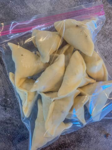 frozen uncooked sambousek in a a plastic ziplock bag
