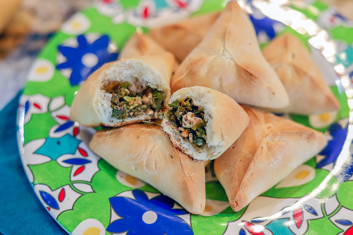 spinach and cheese fatayer on a flowered plate
