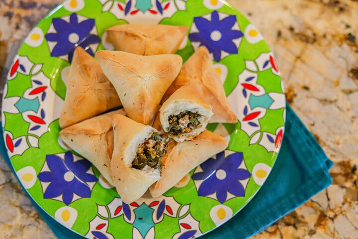 Fatayer on a green flowered plate with a blue napkin folded under it