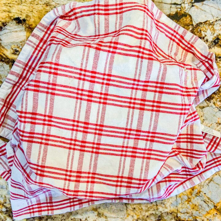 a bowl with a red and white checkered washcloth