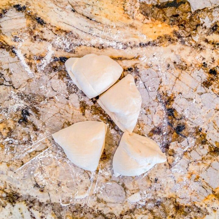 four pieces of dough on a floured surface