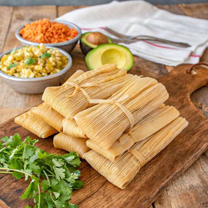 tamales on a cutting board with fixings