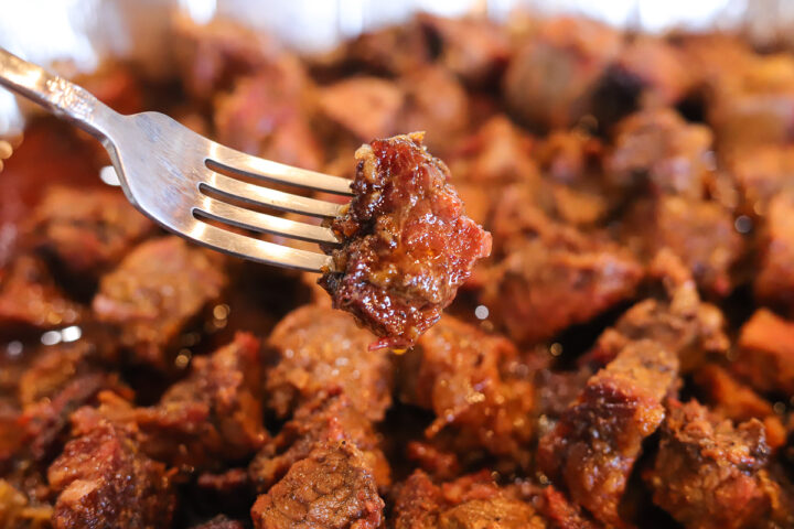burnt ends in a pan and one unclose on a fork