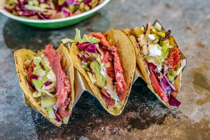 3 corned beef Irish tacos on a taco holder with slaw in the background