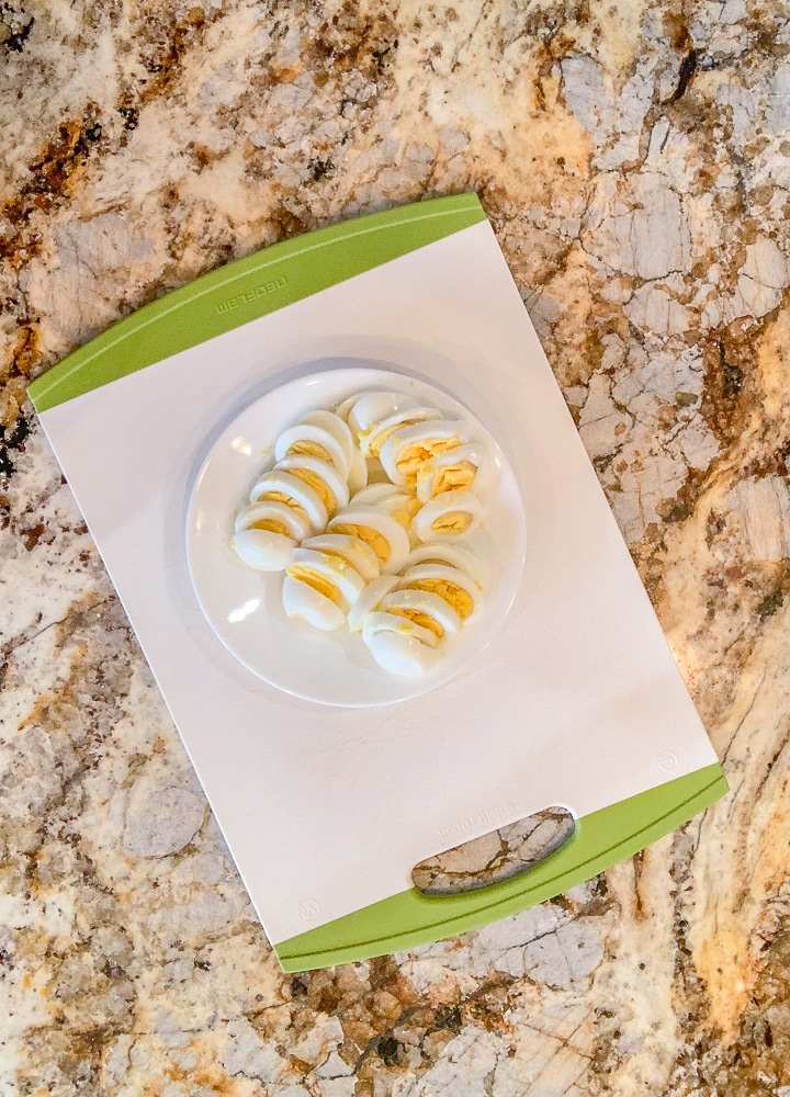 sliced boiled eggs on a white plate on top of a cutting board