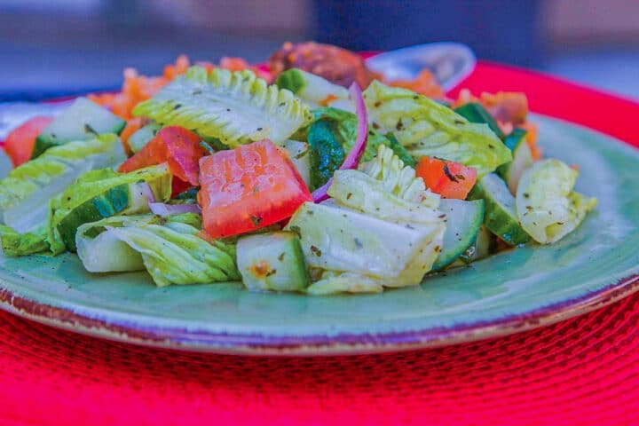 salad on a blue plate over a red mat