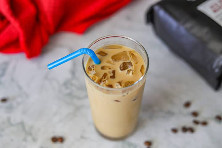 iced latte with a blue straw and coffee beans around it