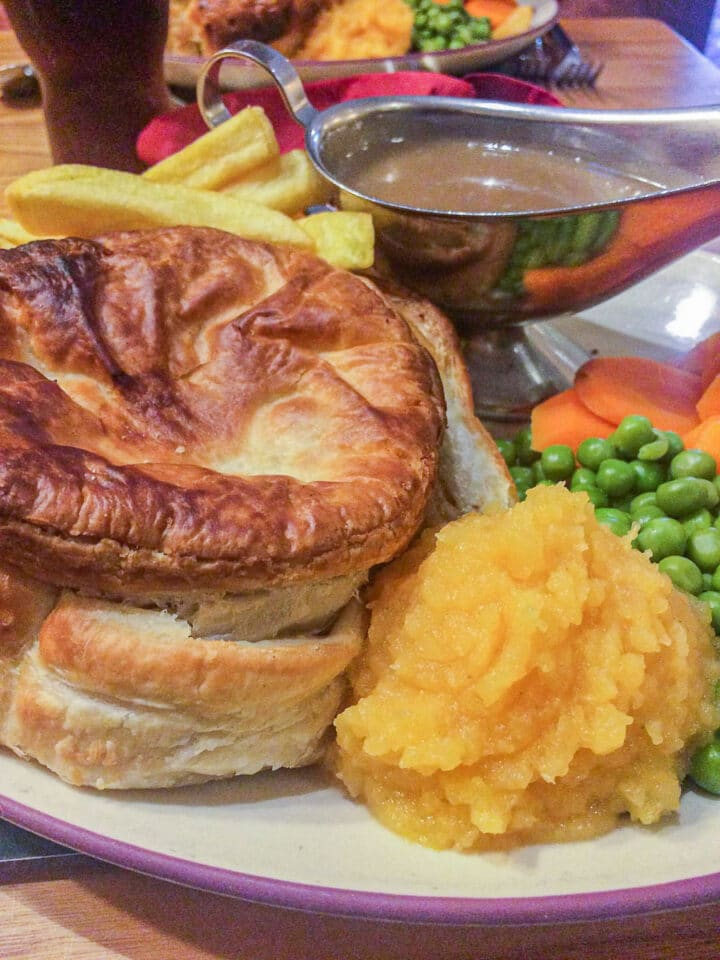 meat pie on a plate with veggies
