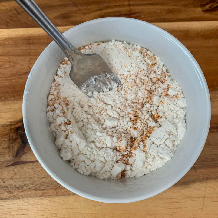 flour and seasoning in a white bowl