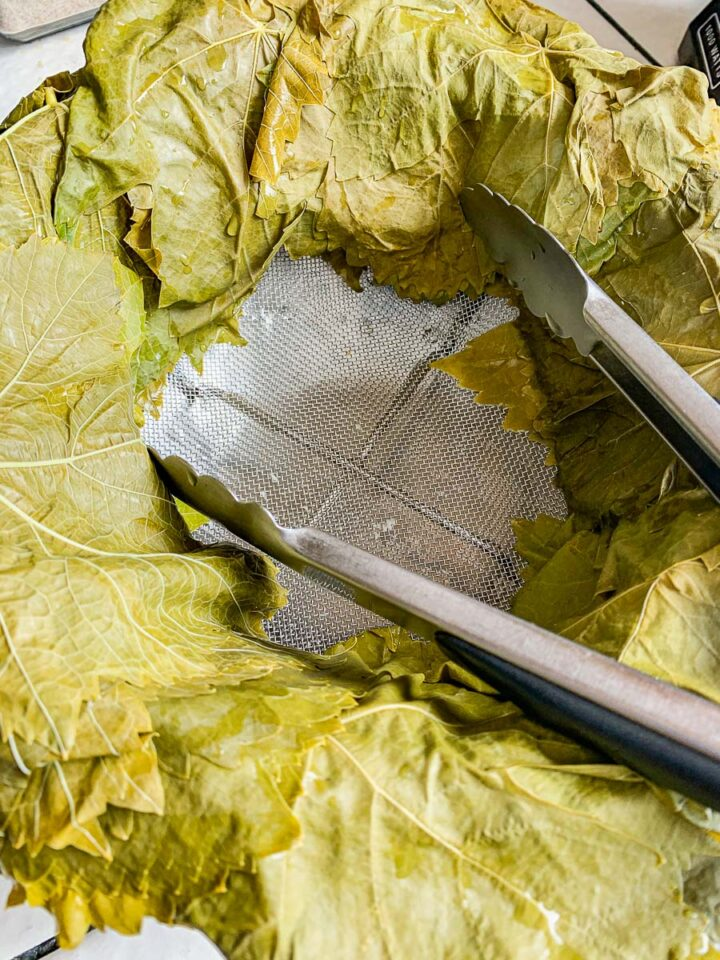 grape leaves draped over a strainer.