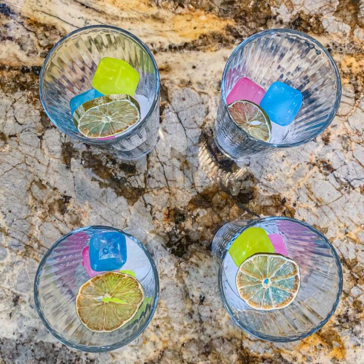 4 glasses with reusable colorful ice cubes and dehydrated lime slices