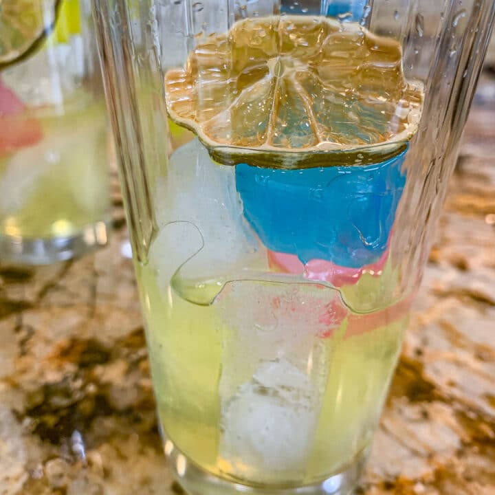 a tall glass with yellow liquid, colorful ice cubes, and sliced lime