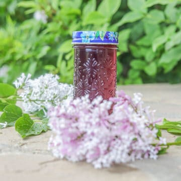 lilac syrup in a bottle surrounded by lilacs