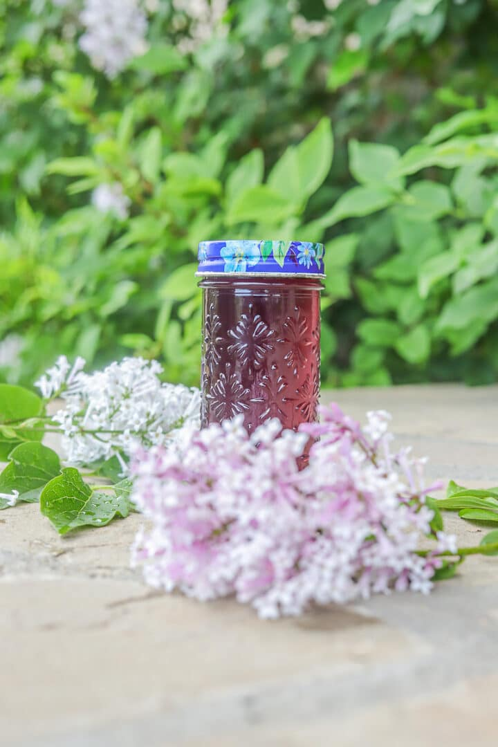 lilac syrup with flowers around it