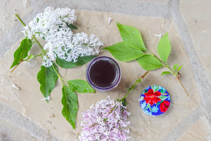 lilac syrup with lilacs around it